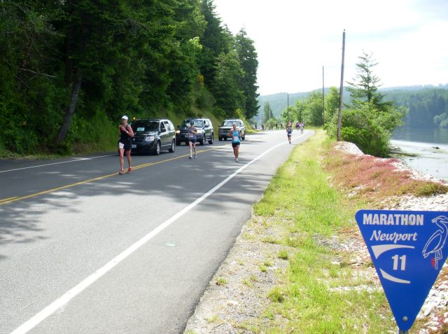 Runners along cars and mile 11 sign post - edited